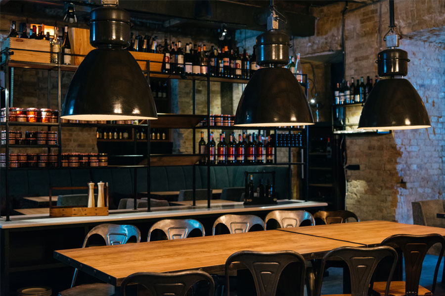 Restaurant interior with wine bottles on large wall rack and wood top tables
