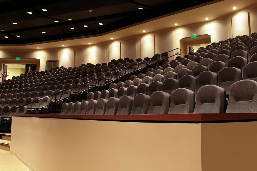 Movie theater with brown chairs and stadium seating