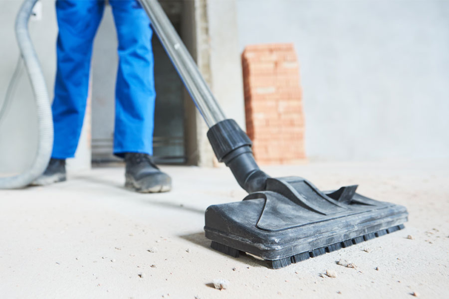 Janitor with blue pants in construction site vacuuming dusty floor