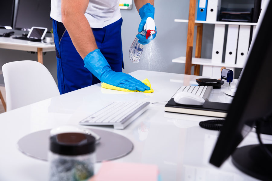 Cleaner with rubber globes using spray bottle to sanitize office desk