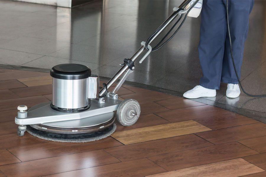Custodian using floor buffing machine on hardwood floor in commercial office