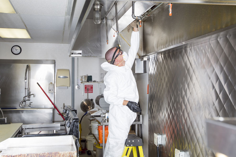 Custodian wearing personal protective gear on ladder cleaning commercial kitchen equipment